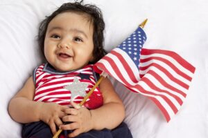 infant holding american flag after acquisition of citizenship