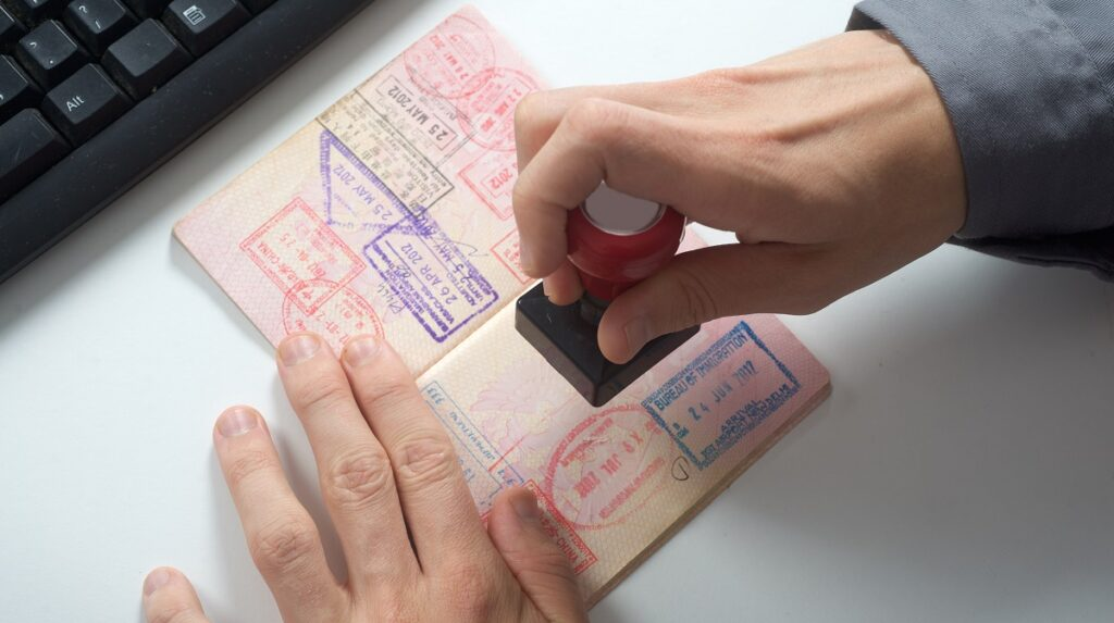CBP immigration officer stamps passport and checks for immigrant intent